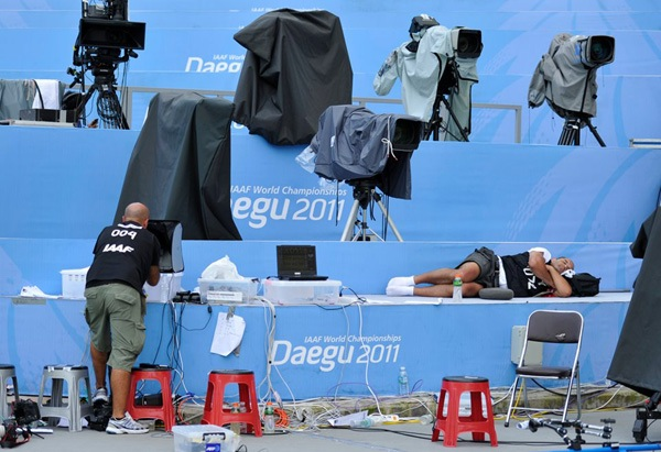Reuters staff photographer Michael Dalder rests duringa break at the IAAF World Championships in Daegu