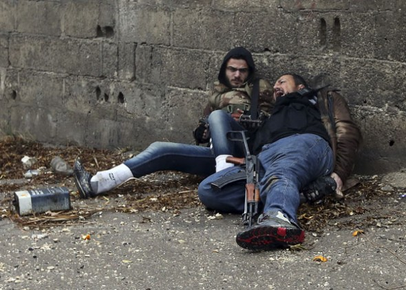 A Free Syrian Army fighter looks at his comrade as he gets shot by sniper fire during heavy fighting in the Ain Tarma neighbourhood of Damascus