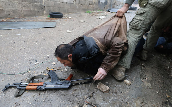 Free Syrian Army fighters pull a fighter who was shot by sniper fire during heavy fighting in the Ain Tarma neighbourhood of Damascus
