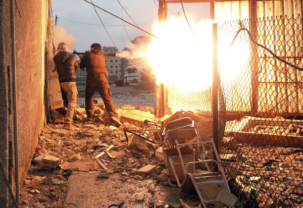 A Free Syrian Army fighter fires a rocket propelled grenade (RPG) during heavy fighting in the Ain Tarma neighbourhood of Damascus