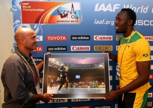 Morin átadja Boltnak a róla készült képét - Fotó: AFP