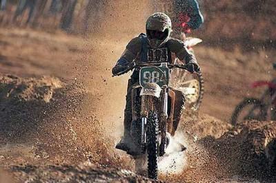"""Emberi szöveg: Egy személy motorozik egy sár borította motoron"""" Gépi szöveg: </ Egy személy motorozik egy földúton"""