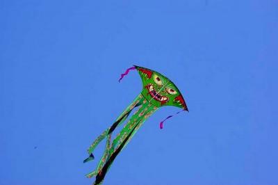 """Emberi szöveg: """"Egy zöld sárkány szörny repül a napos égbolton."""" Gépi szöveg: """"Egy férfi repül a levegőben  szörfözés közben."""" Készítő ismeretlen."""