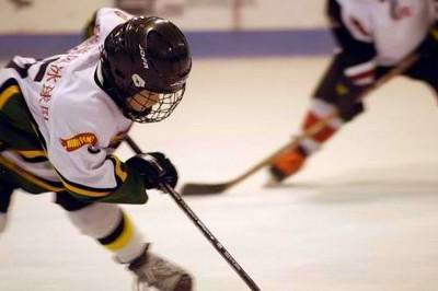 """Emberi szöveg: Egy fatal hoki játékos játszik a jégen. Gépi szöveg: """"Két hoki játékos küzd a korongért"""